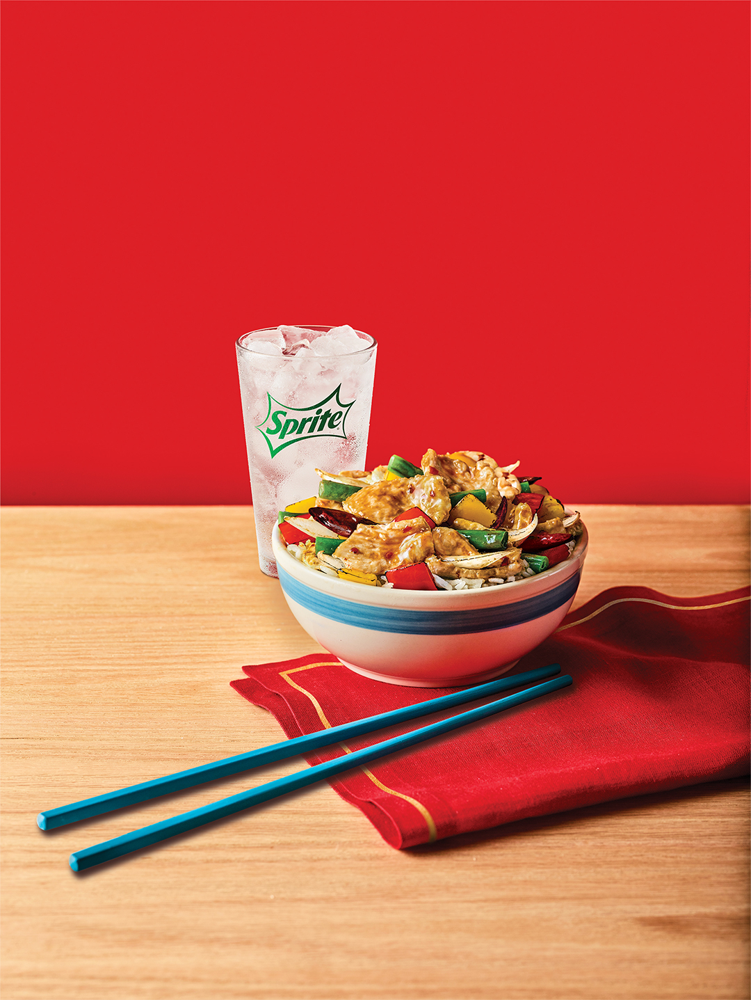 Panda Express Firecracker Chicken Bowl with cup of Sprite, on a wooden table.
